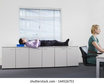 Businessman sleeping on office cabinets while woman working in foreground