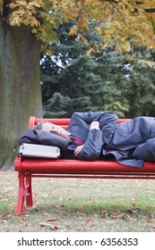 Businessman sleeping on a red parkbench in fall