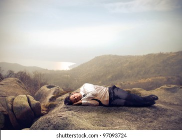 Businessman sleeping on a rock