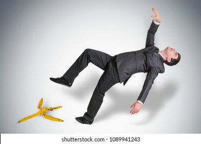 Businessman slipping and falling from a banana peel - business risk concept