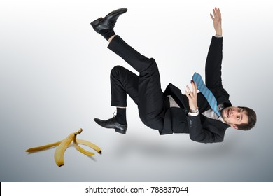 Businessman slipping on a banana peel.