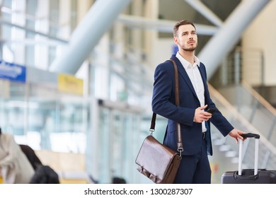 Businessman with smartphone in the airport. Terminal looks after his connecting flight