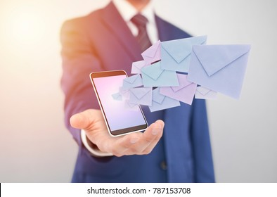 Businessman with smartphone with envelopes coming out of the screen