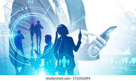 Businessman with smartphone and his team working in city with double exposure of online work interface. Toned image. Elements of this image furnished by NASA
