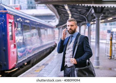 Businessman with smartphone, making a phone call, train platform