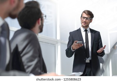 businessman with a smartphone standing in his ofiice