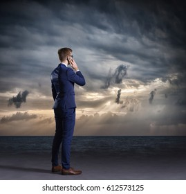 Businessman with smartphone standing on a dark, dramatic ocean background. Business concept.