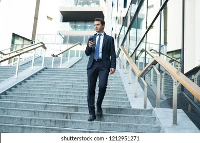 Businessman with smartphone walking in city street
