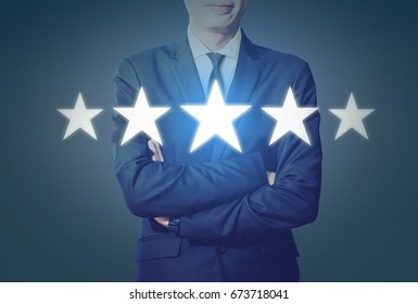 Businessman Smile and Look at Five Star Symbol Increase Rating and Dark Blue Background with Copy Space, Excellence Concept.