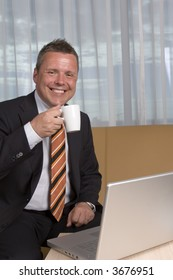 Businessman smiling at camera drinking coffee and working on laptop
