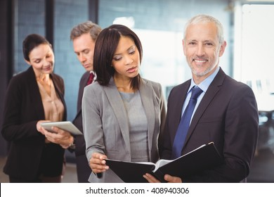 Businessman smiling at camera while businesswoman looking into organizer and two colleagues interacting in the background