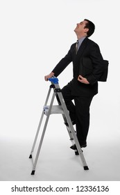 Businessman smiling as he climbs up a stepladder, briefcase in hand. Isolated against a white background
