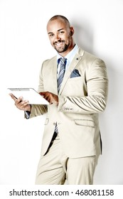 Businessman smiling into the camera leaning against a white wall and working on a tablet