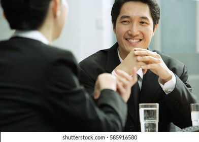 Businessman smiling, at woman in front of him