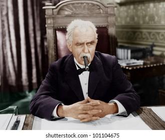 Businessman smoking cigar at desk