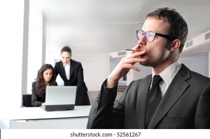 Businessman smoking with two businesswomen on the background