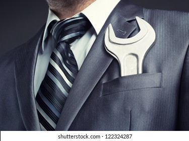 Businessman with spanner in suit pocket