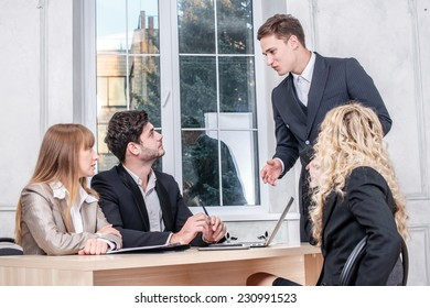 Businessman speaking at the meeting. The head of a businessman talking to colleagues at a meeting. Businesspeople sitting at the table and look at the head of the company