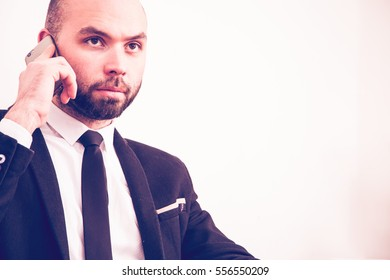 Businessman is speaking on the mobile phone on the gray background