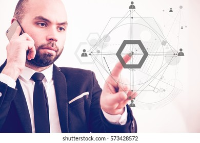 Businessman speaking on the phone and pointing to the drawn human connection scheme.