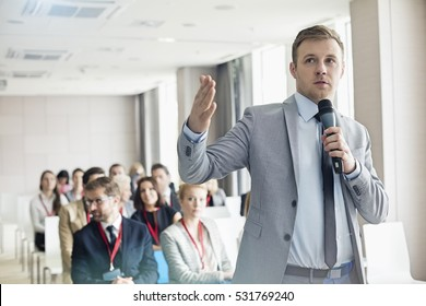 Businessman speaking through microphone during seminar in convention center