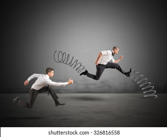 Businessman with spring runs against another businessman