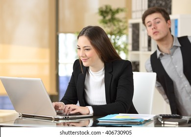 Businessman spying his colleague who is working at her desktop at job