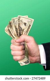 A businessman squeezes a fist full of cash.