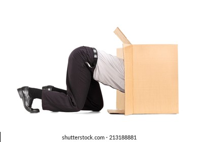 Businessman squeezing himself into a box isolated on white background