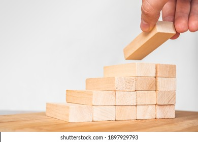 Businessman stacking wooden blocks. Hand arranging wood block stacking as step stair. Ladder career path concept for business growth success process