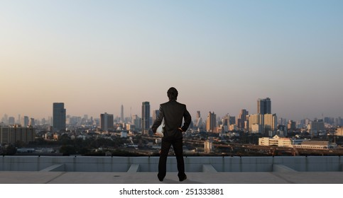 businessman stand on roof top of skyscraper, business concept