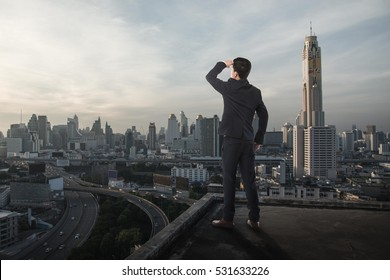 Businessman stand on roof top of city view, business globalization concept