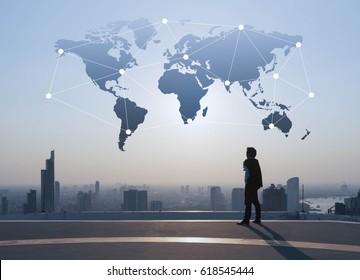 ビジネスマンが建物の屋根の上に立ち、グローバル化のコンセプト