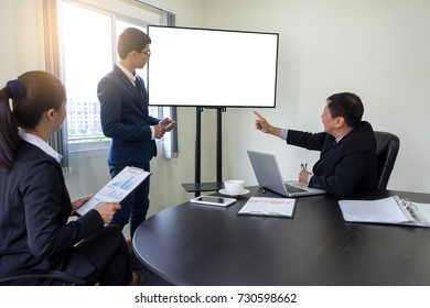 businessman stand to presentation in business group meeting with Businesswoman and with big monitor white screen with clipping path