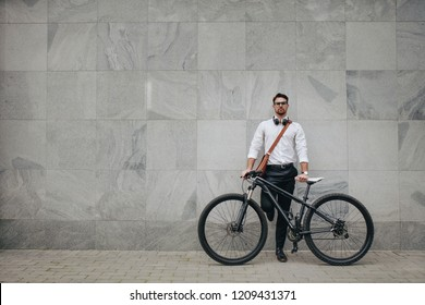 Businessman standing against a building wall in the street holding his bike. Man in formal clothes wearing office bag and headphones around the neck standing with his bicycle.