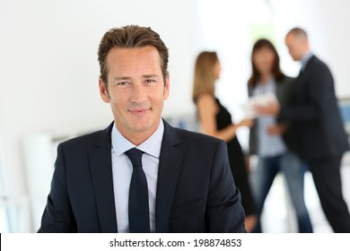 Businessman standing with arms crossed, people in background