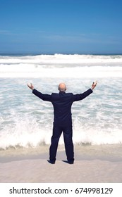 Businessman Standing With Arms Outstretched at the Beach