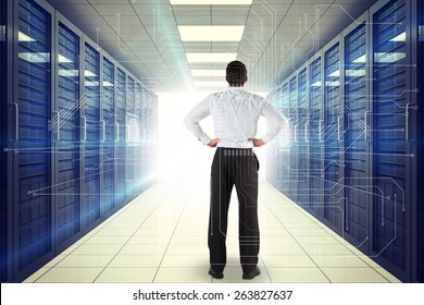 Businessman standing back to the camera with hands on hips against digitally generated server room with towers