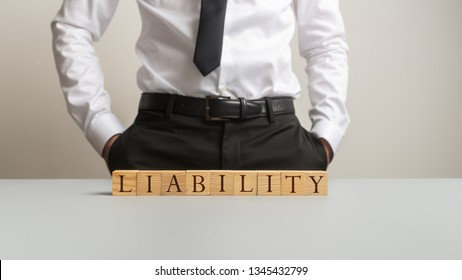 Businessman standing behind an office desk with a Liability sign on it in a conceptual image of obligation and responsibility.