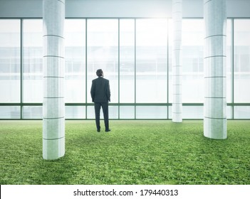 Businessman standing in bright modern office with green grass floor