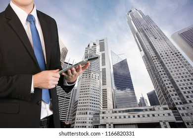 Businessman standing with business building background. Businessman using tablet with virtual interface screen as concept of industry 4.0.