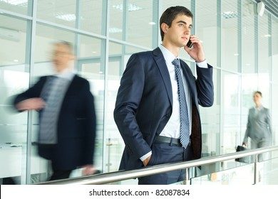 Businessman standing by banisters and calling with walking people on background