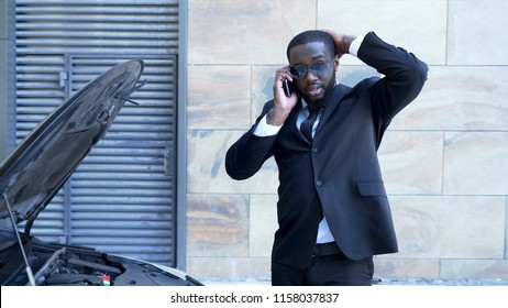Businessman standing by broken car with open hood, talking over phone, breakdown