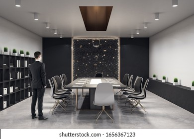 Businessman standing in conference interior hall with books on shelf and document on table.  Workplace and lifestyle concept.