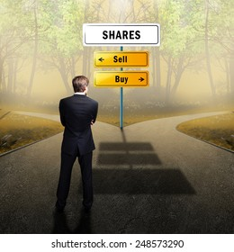 businessman standing at a crossroad having to decide whether to sell or buy shares