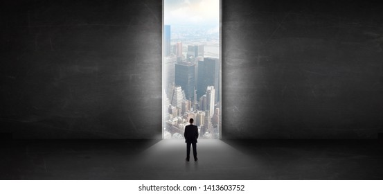 Businessman standing in a dark room and looking outside to a cityscape view