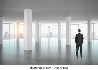Businessman standing in empty office interior with panoramic window, new york city view and daylight. Research concept.