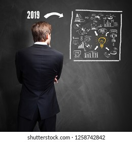 businessman standing in front of a blackboard with plan for 2019 written on it