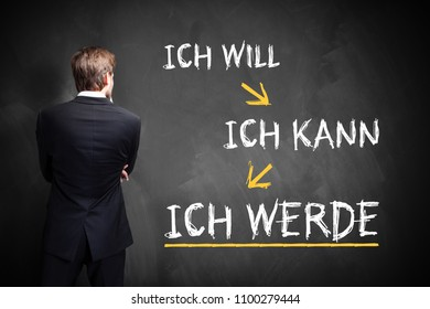 "businessman standing in front of a chalkboard the message ""I want, I can, I will"" in Germanaa"