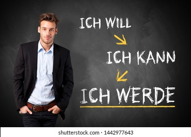 "businessman standing in front of a chalkboard the message ""I want, I can, I will"" in German"